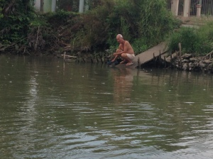 Local older man sitting by the river